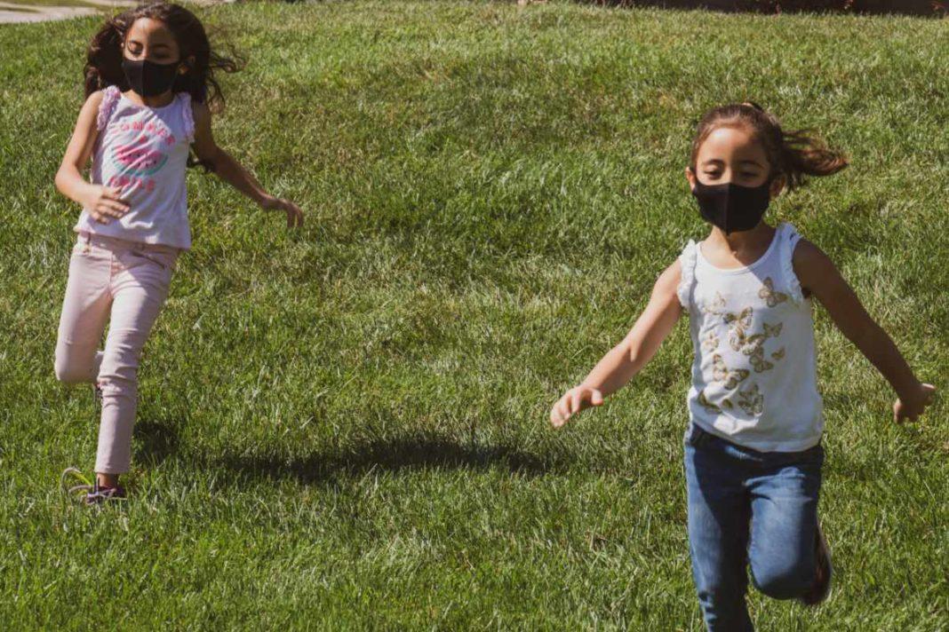 Zwei spielende Kinder mit Maske auf einer grünen Wiese.