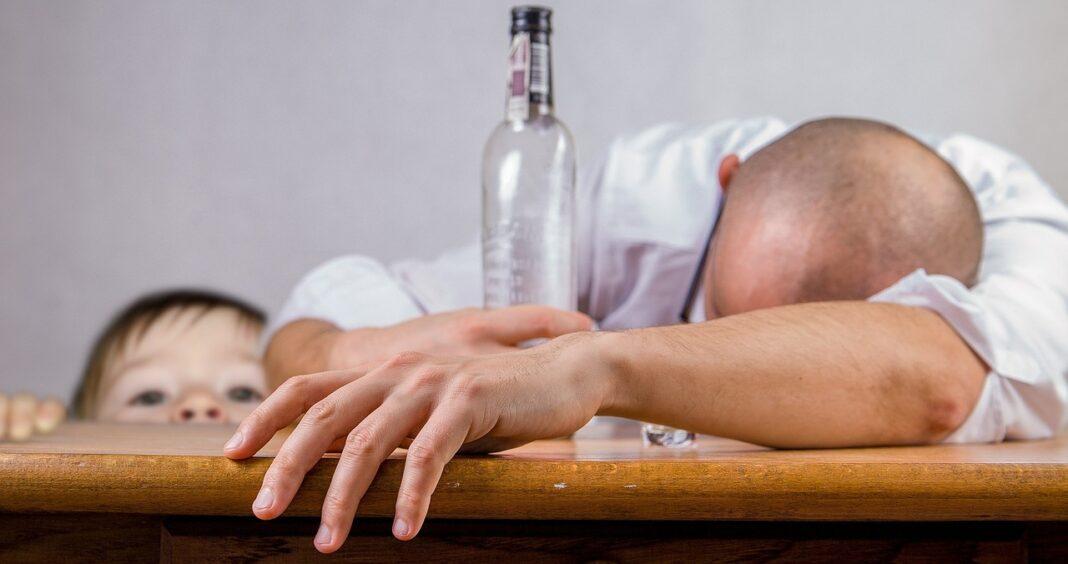 Betrunkener Mann mit Alkoholflasche in der Hand und ein neugieriges Kind, das auf den Tisch schaut.