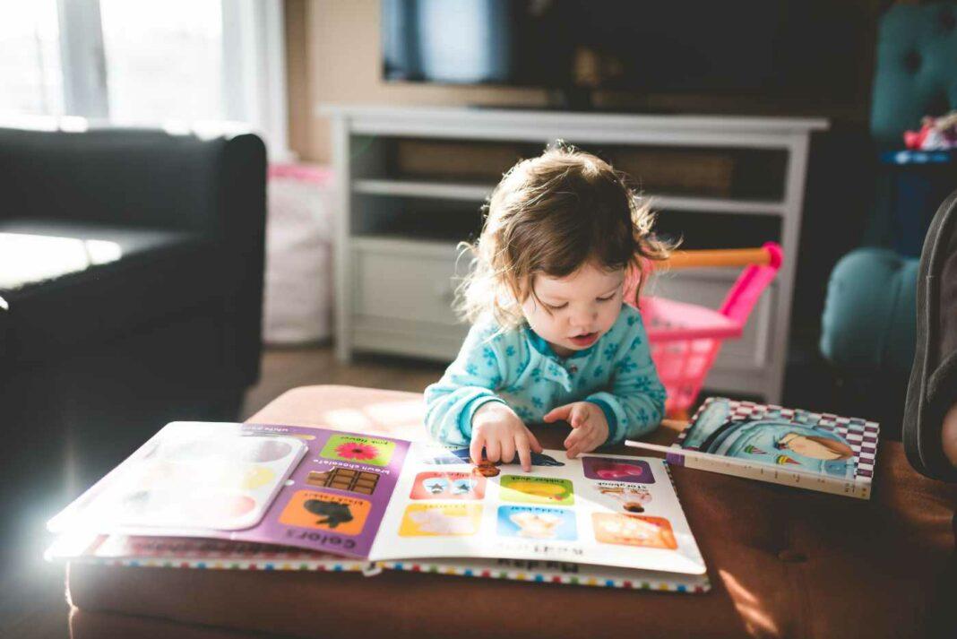 Ein Kindergartenkind beim Betrachten eines Bilderbuchs.